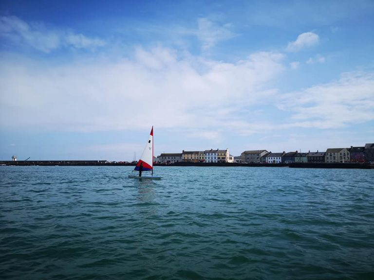 Topper sailing across the Donaghadee Harbour skyline